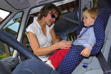frau setzt kind in auto in kindersitz eltern. Black Bedroom Furniture Sets. Home Design Ideas
